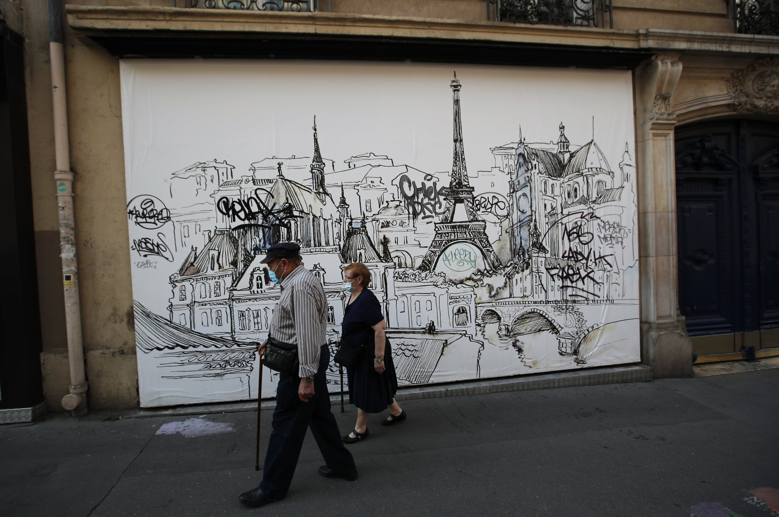 A couple wearing protective masks take a walk during a nationwide confinement to counter the COVID-19, in Paris Friday April 10, 2020. (AP Photo)