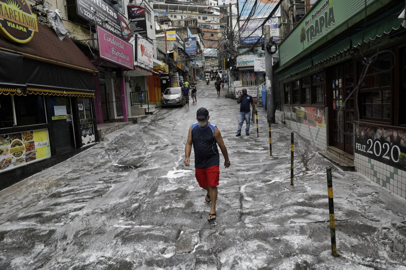 A man wearing a protective mask walks on a street disinfected by cleaners during the  COVID-19 outbreak, at the Rocinha slum in Rio de Janeiro, Brazil April 10, 2020. (REUTERS Photo)