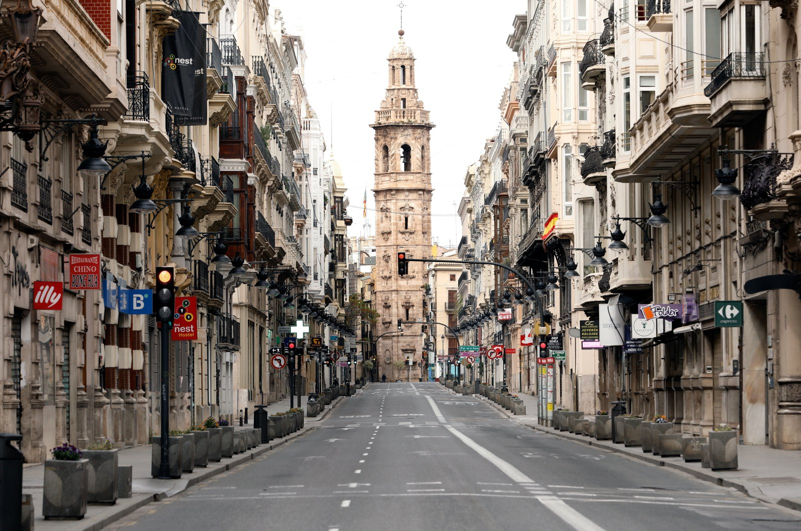 View of a church tower at the end of a deserted street in Valencia, eastern Spain, April 11, 2020. For the first time in centuries, many church bells across Spain will not be ringing on the eve of Easter Sunday, as most bell-ringers won't be able to access their churches and cathedrals due to the nationwide lockdown imposed by the government in a bid to slow down the spread of the pandemic COVID-19 disease. (EPA Photo)