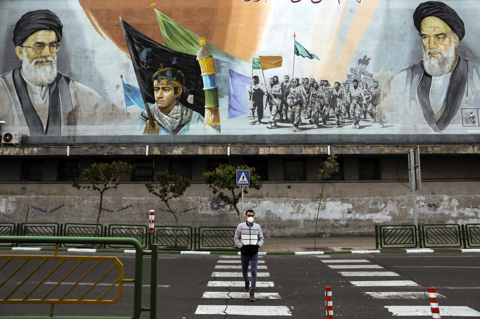 A man crosses an empty street under portraits of the late Iranian revolutionary founder Ayatollah Khomeini, right, and Supreme Leader Ayatollah Ali Khamenei, left, in Tehran, Iran, April 3, 2020 photo, . (AP Photo)
