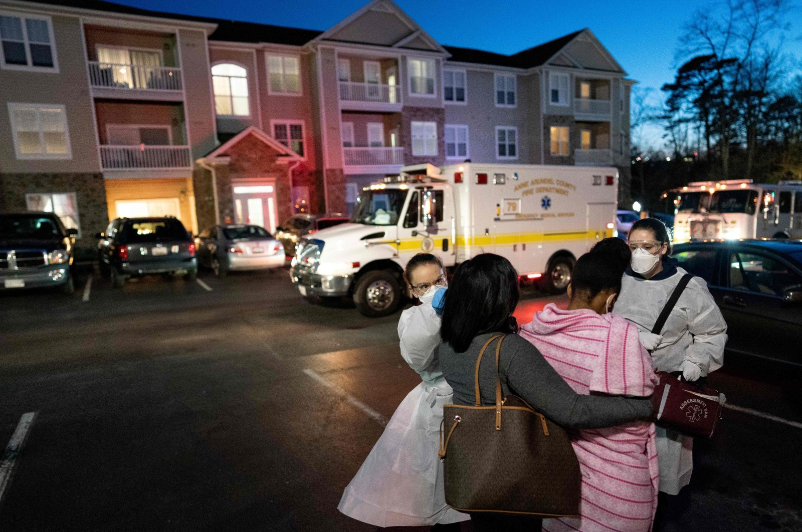 Emergency medical technicians with Anne Arundel County Fire Department assess a young woman experiencing COVID-19 symptoms in Glen Burnie, Maryland on April 10, 2020. (AFP Photo)