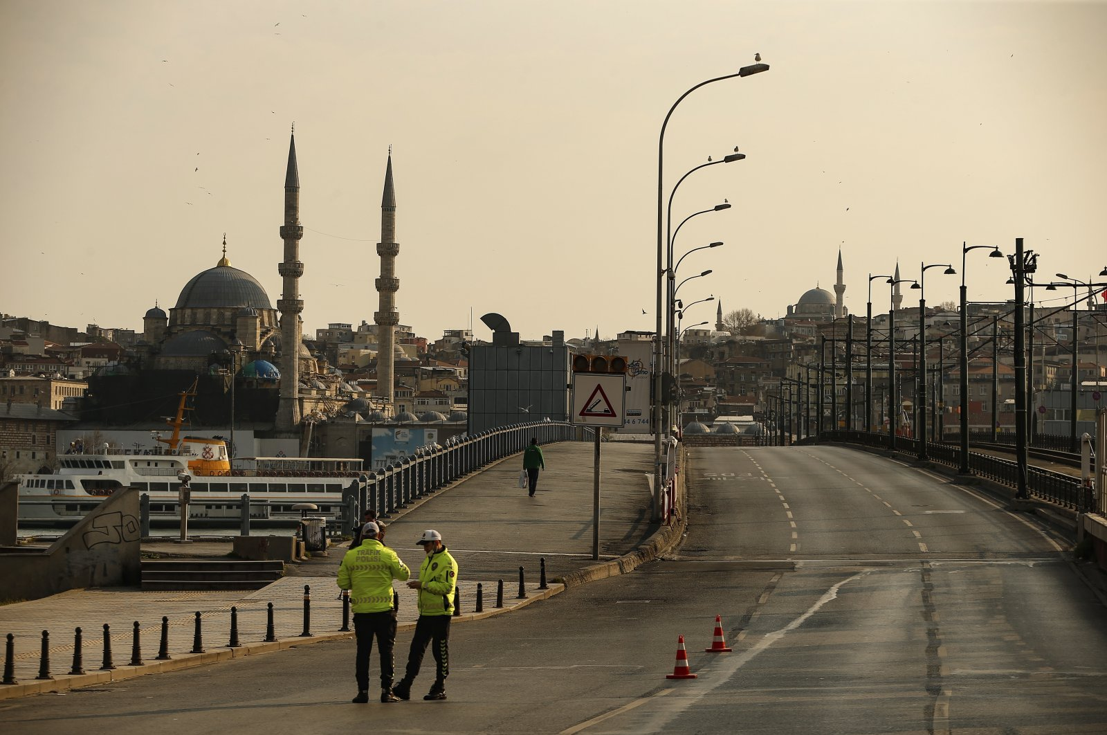 Police officers stand in the normally crowded but now mostly deserted Galata Bridge over Golden Horn with New Mosque in the background hours after the two-day curfew declared by the government to slow coronavirus spread, in Istanbul, Saturday, April 11, 2020. (AP Photo)