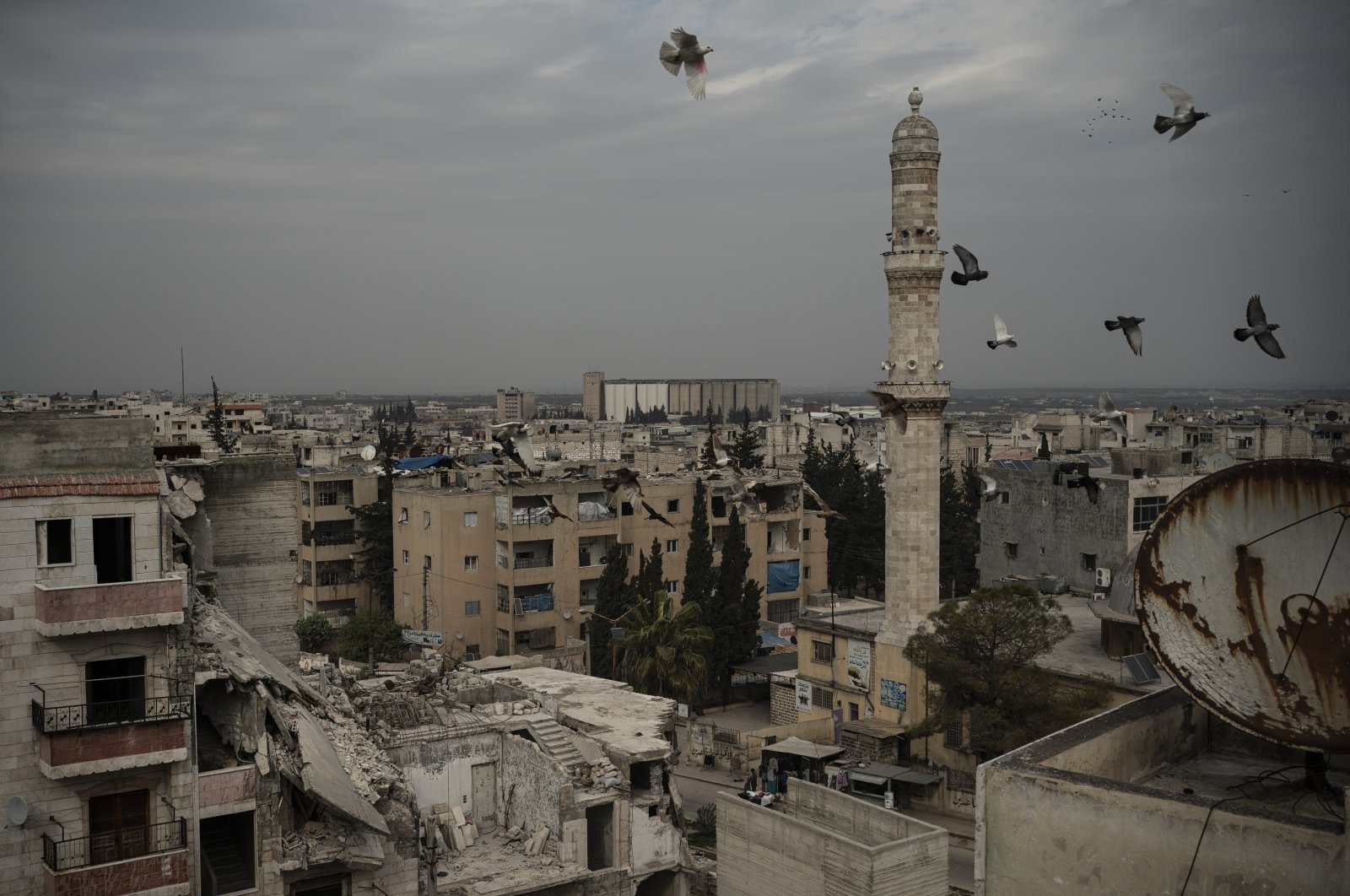 A mosque stands next to a damaged building, in Idlib, Syria, March 12, 2020.