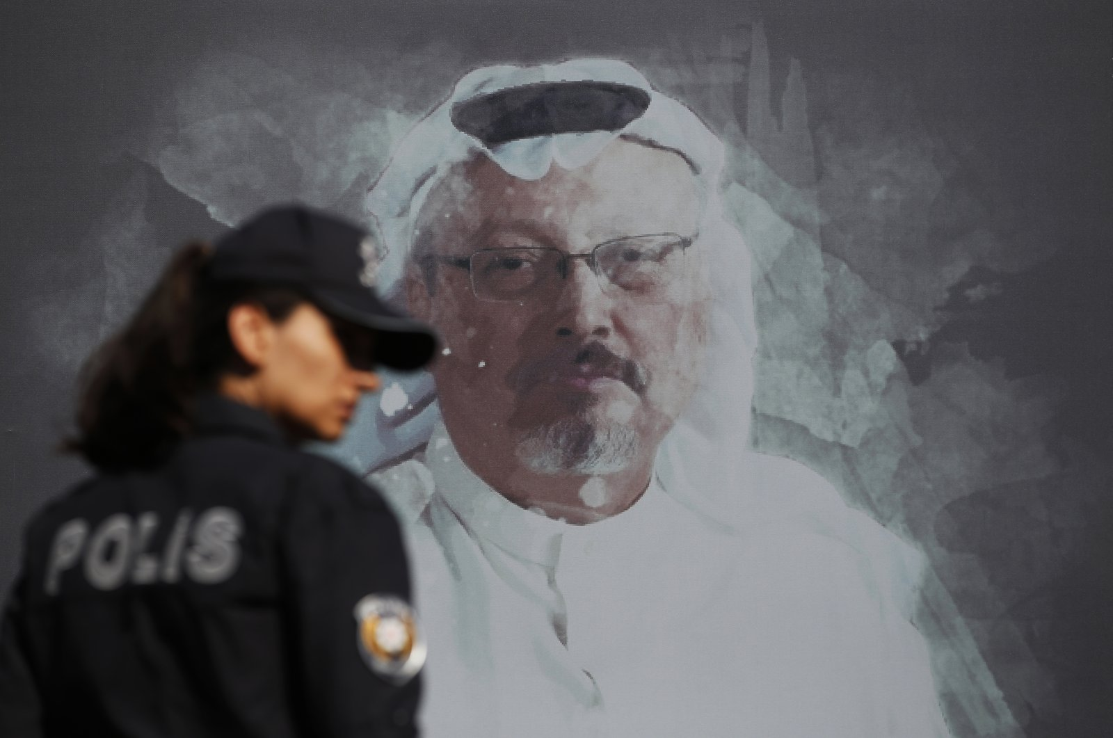 A Turkish police officer walks past a picture of slain Saudi journalist Jamal Khashoggi prior to a ceremony, near the Saudi Arabia consulate in Istanbul, marking the one-year anniversary of his death, Oct. 2, 2019. (AP Photo)