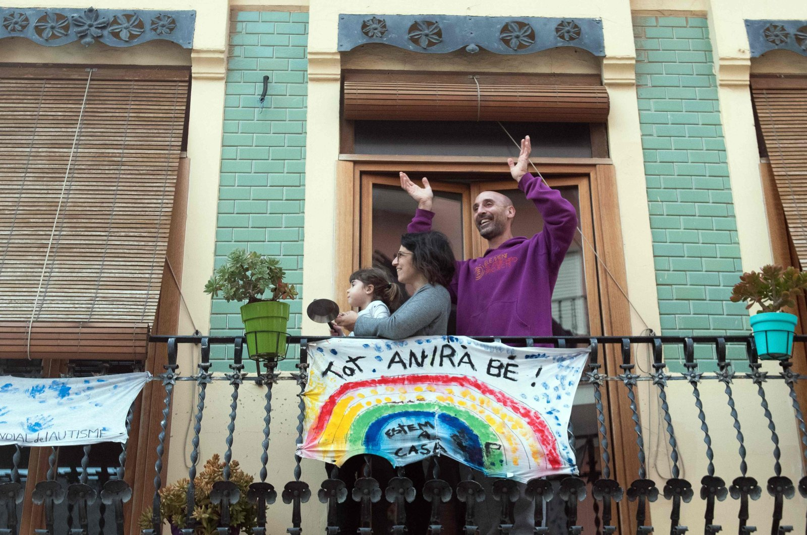"""A family applauds from their balcony, adorned with a banner reading """"Everything will be ok,"""" in El Cabanal, Valencia, April 9, 2020. (AFP Photo)"""