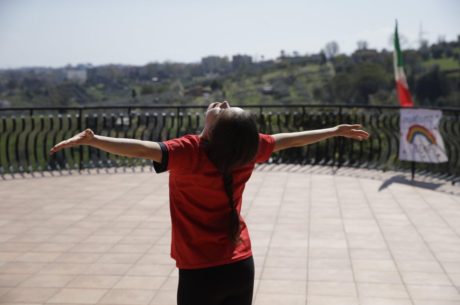 Arianna Sacripante trains on her terrace in Monterotondo, Italy, April 3, 2020. (AP Photo)