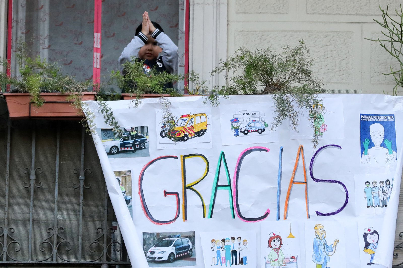 A child gestures from the balcony of his house in support of healthcare workers, in front of the Dos de Maig Hospital, Barcelona, Apr.11, 2020. (REUTERS Photo)