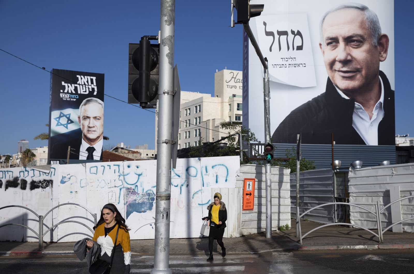 People walk next to election campaign billboards showing Israeli Prime Minister Benjamin Netanyahu (R) and Benny Gantz (L), Bnei Brak, March 1, 2020. (AP Photo)
