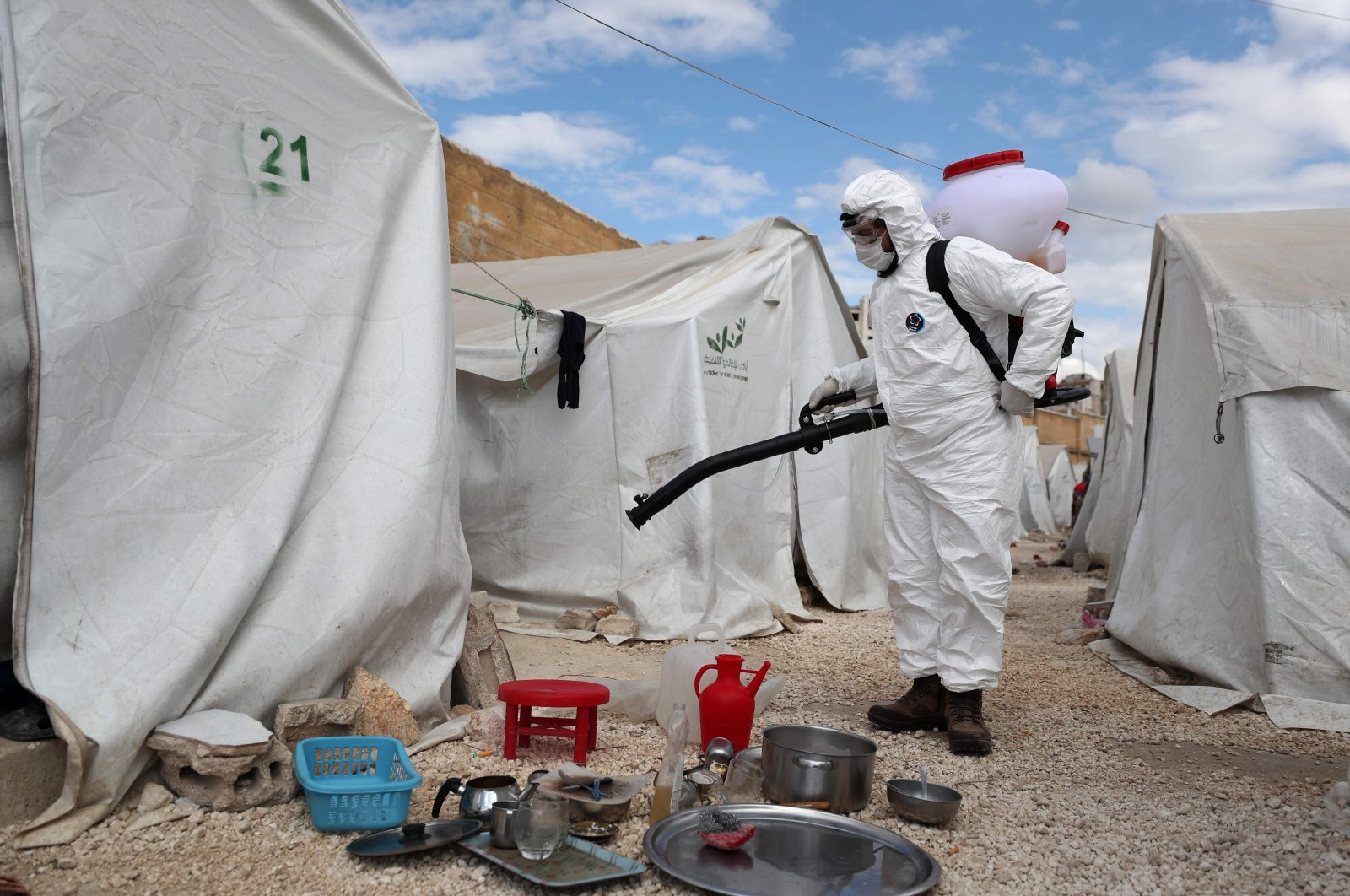 A sanitation worker disinfects a camp for displaced Syrians next to the Idlib municipal stadium in the northwestern Syrian city, Thursday, April 9, 2020. (AFP)
