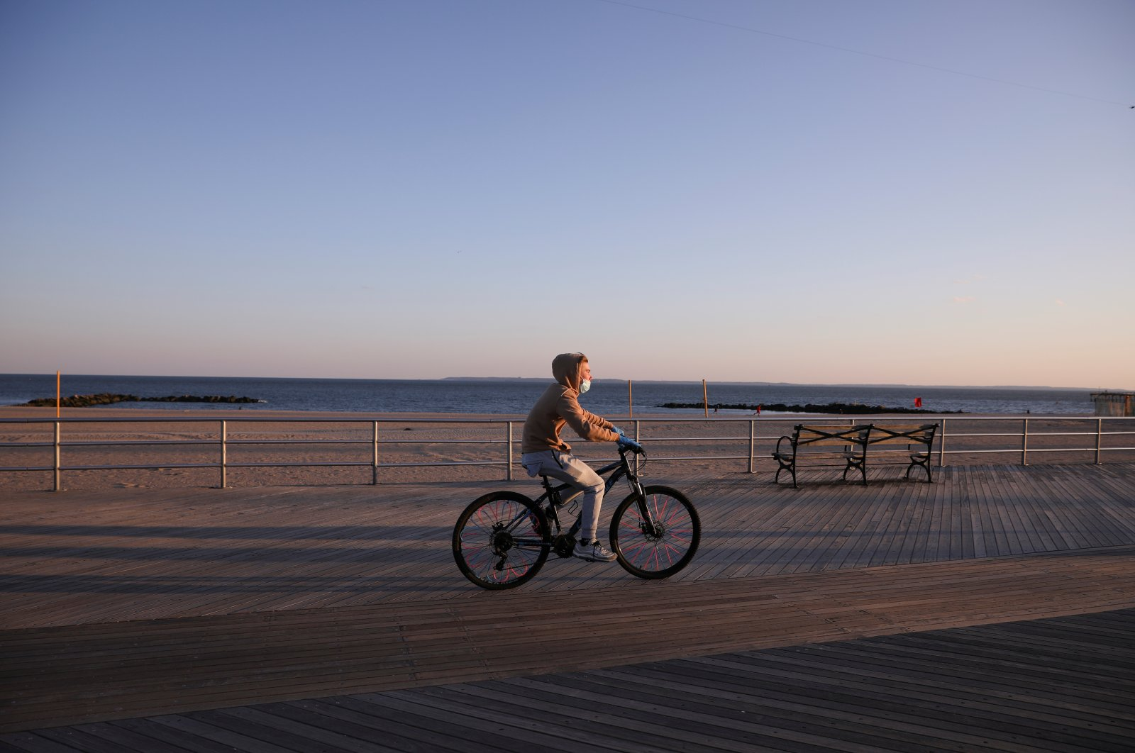 A bicyclist wears a mask and cycles along the mostly empty Coney Island boardwalk, Brooklyn, New York, U.S., April 11, 2020. (REUTERS Photo)