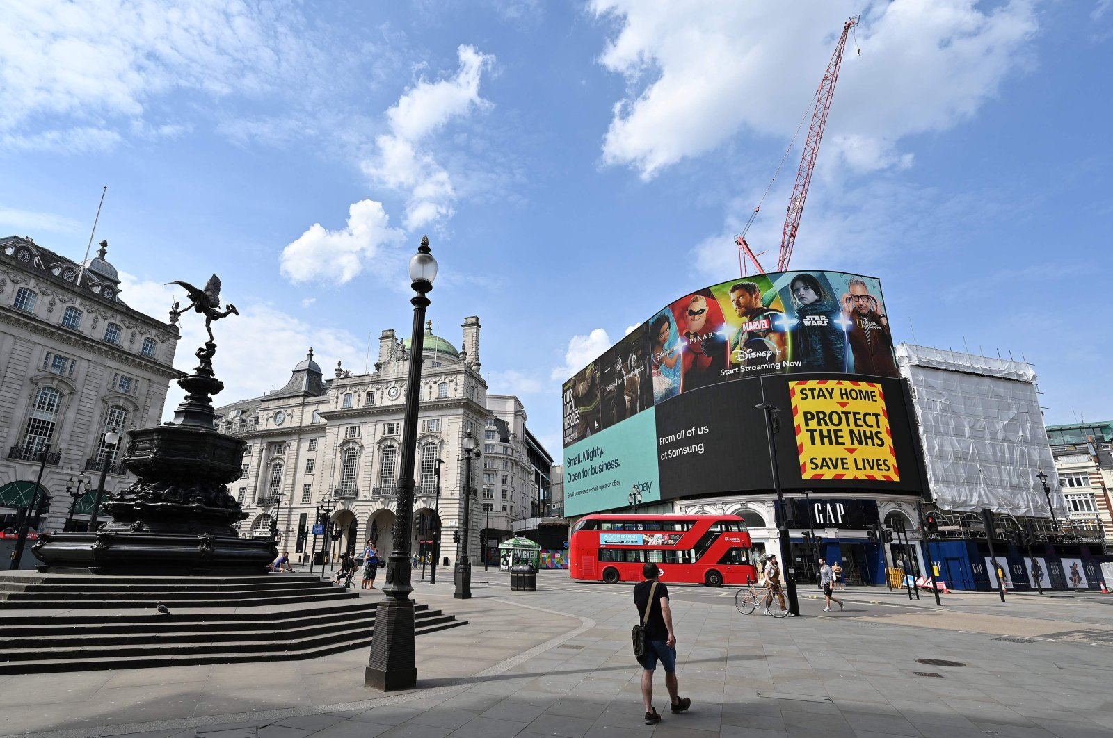 """The electronic billboard in Piccadilly Circus displays a notice telling people to """"Stay Home. Protect the NHS. Save Lives."""" near the empty Shaftesbury Memorial Fountain, London, April 12, 2020. (AFP Photo)"""