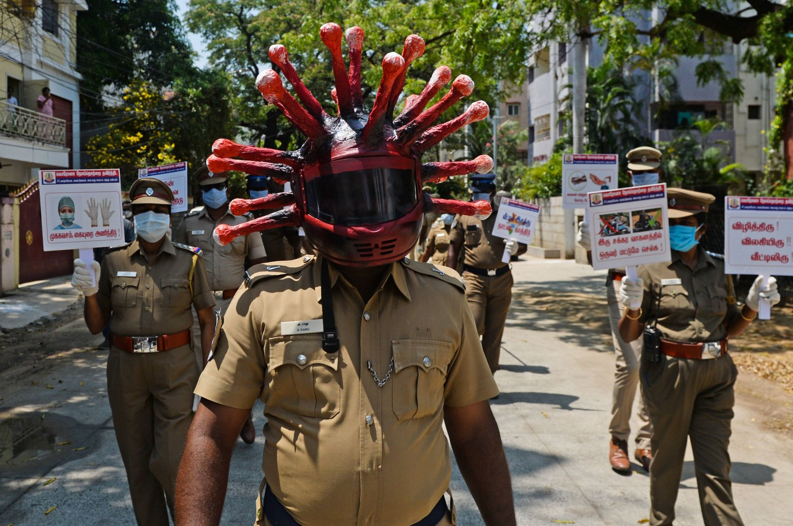 A policeman wearing a coronavirus helmet takes part with others in a procession to raise awareness about the COVID-19 coronavirus during a government-imposed nationwide lockdown, Chennai, Sunday, April 12, 2020. (AFP Photo)