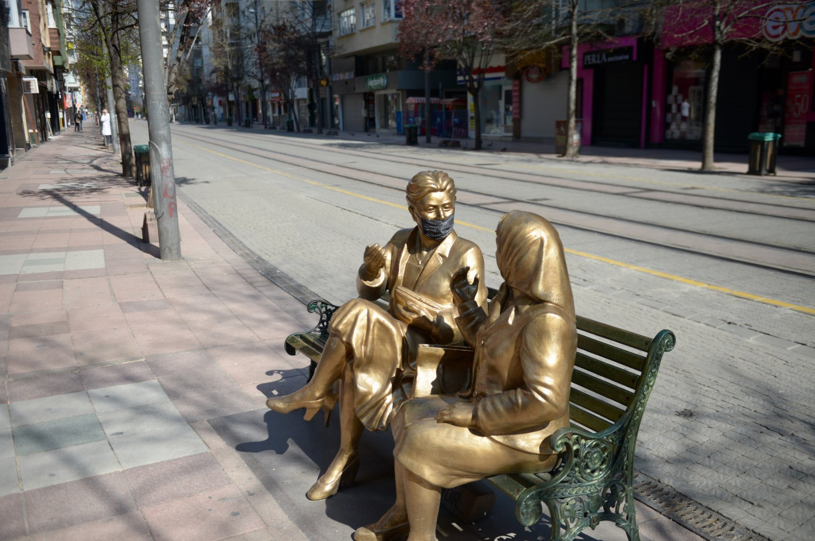 A statue of two women chatting on a bench, one of whom is wearing a face mask, is seen in Turkey's central Eskişehir province, April 12, 2020. (AA Photo)