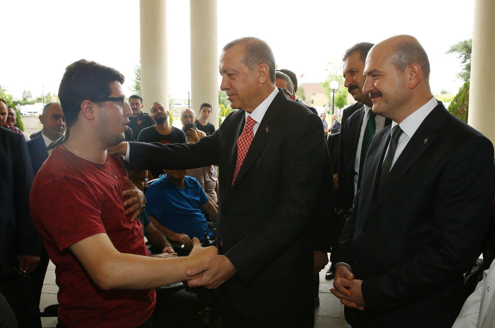 President Recep Tayyip Erdoğan (C) and Interior Minister Süleyman Soylu (R) visit wounded veterans at a rehabilitation hospital in Ankara, Turkey, July 5, 2017. (Sabah Photo via the Presidential Complex)