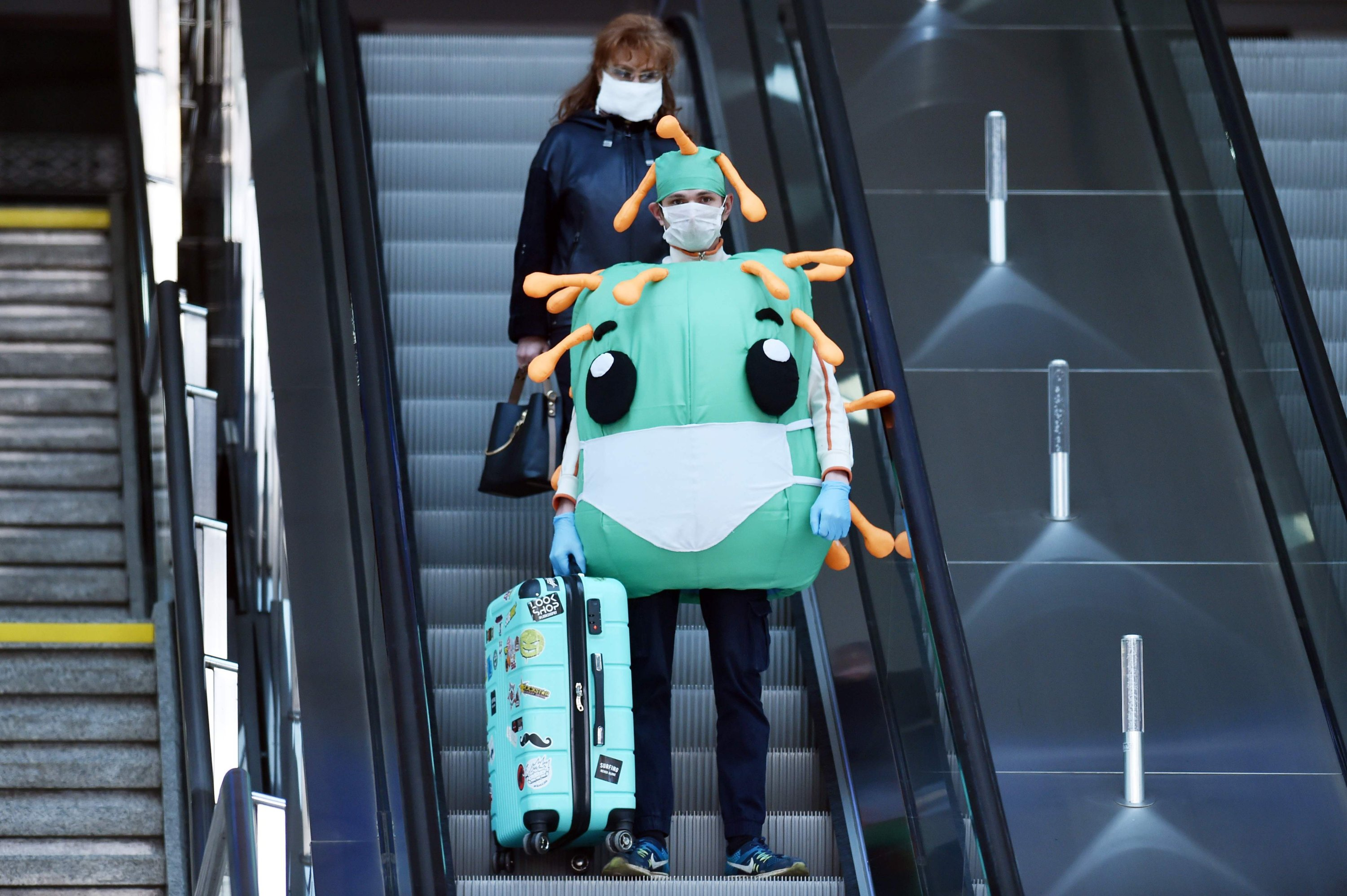 A man wearing a coronavirus costume and a face mask stands on the escalator of a railway station in Minsk on April 11, 2020. (AFP Photo)