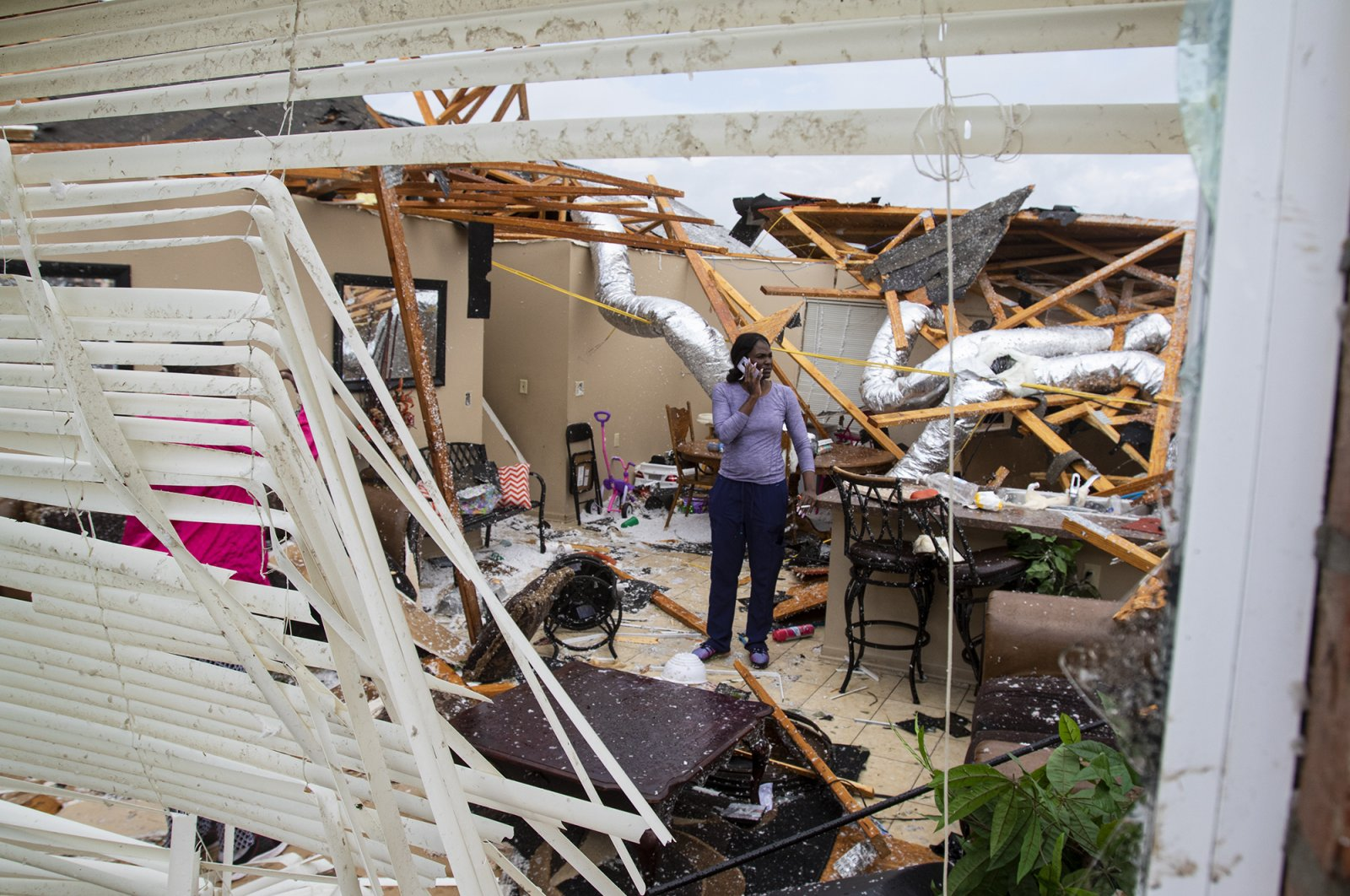 Rolanda Robinson calls family and friends from her brother's damaged home in Monroe, La. after a tornado ripped through the town on Sunday, April 12, 2020. (AP Photo)