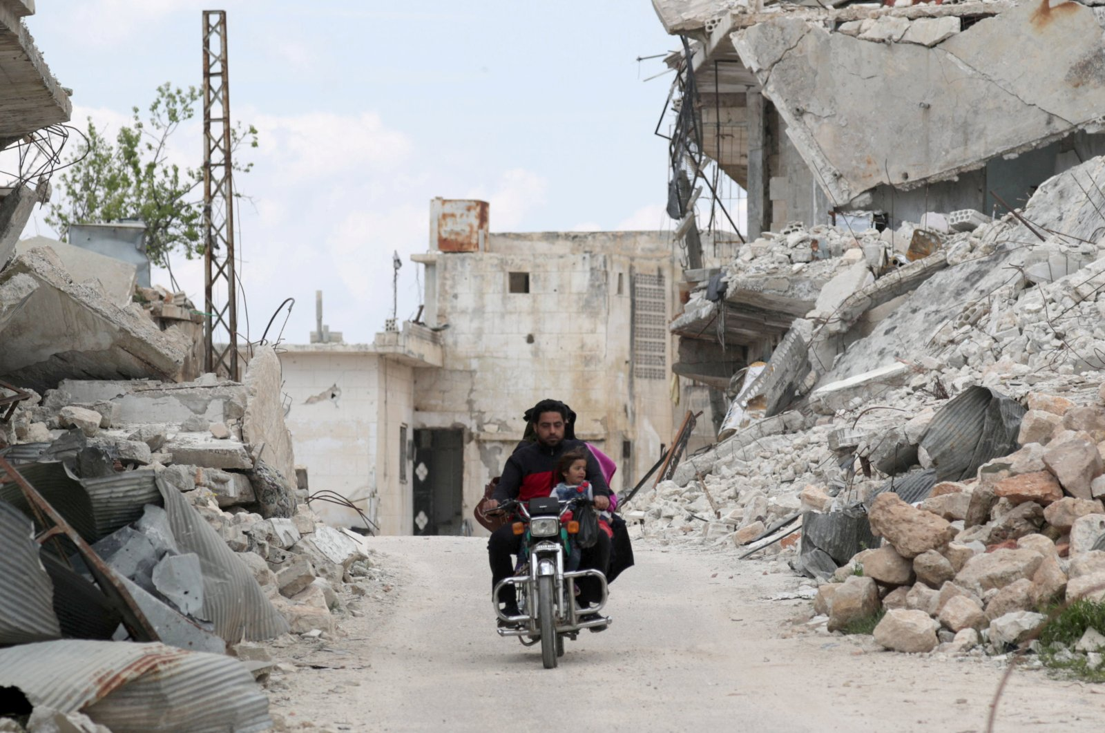 People ride on a motorbike near the rubble of damaged buildings during the coronavirus disease (COVID-19) outbreak in Jabal al-Zawiya, Syria April 12, 2020. (Reuters Photo)
