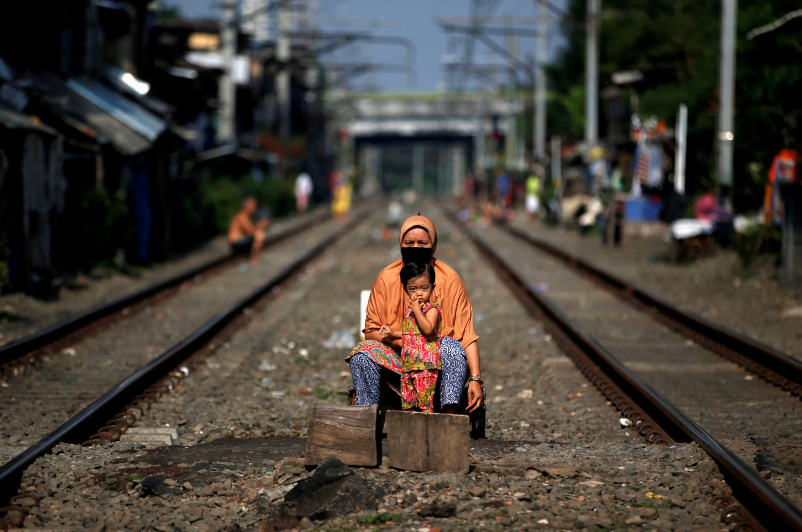 A woman wearing a face mask and a child sit between rail tracks, during the imposition of large-scale social restrictions by the government to prevent the spread of the coronavirus disease in Jakarta, Indonesia, April 12, 2020. (Reuters Photo)