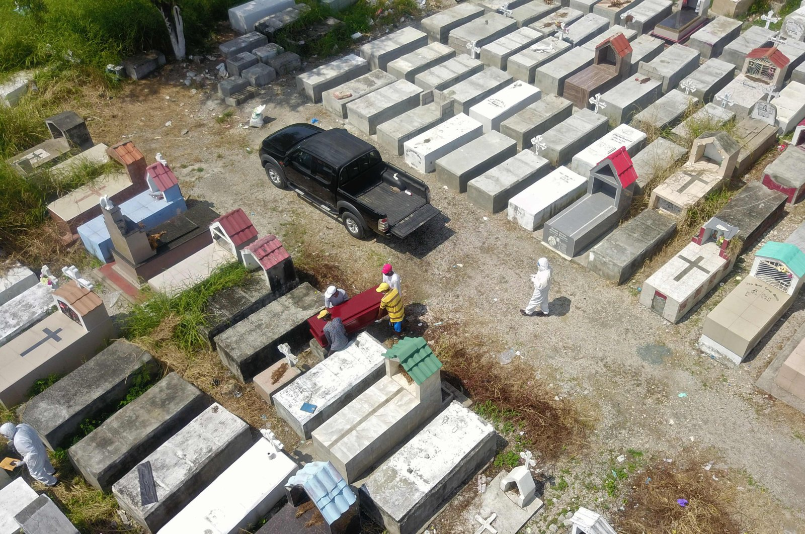 An aerial view of workers burying a coffin at Maria Canals cemetery in the outskirts of Guayaquil, Ecuador, April 12, 2020. (AFP Photo)