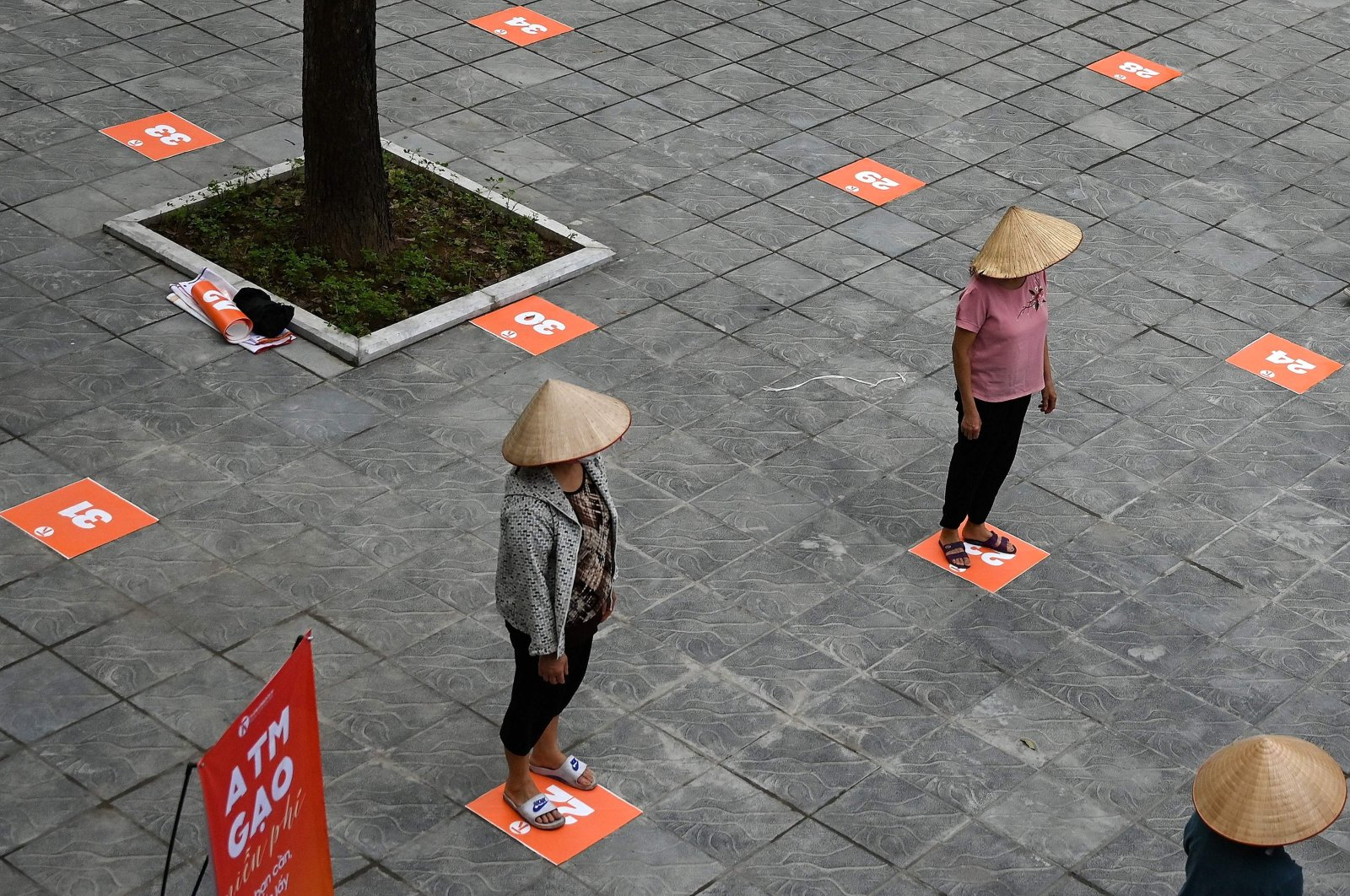 Residents wearing face masks practice social distancing as they wait in a queue for free rice, Hanoi, April 11, 2020. (AFP Photo)