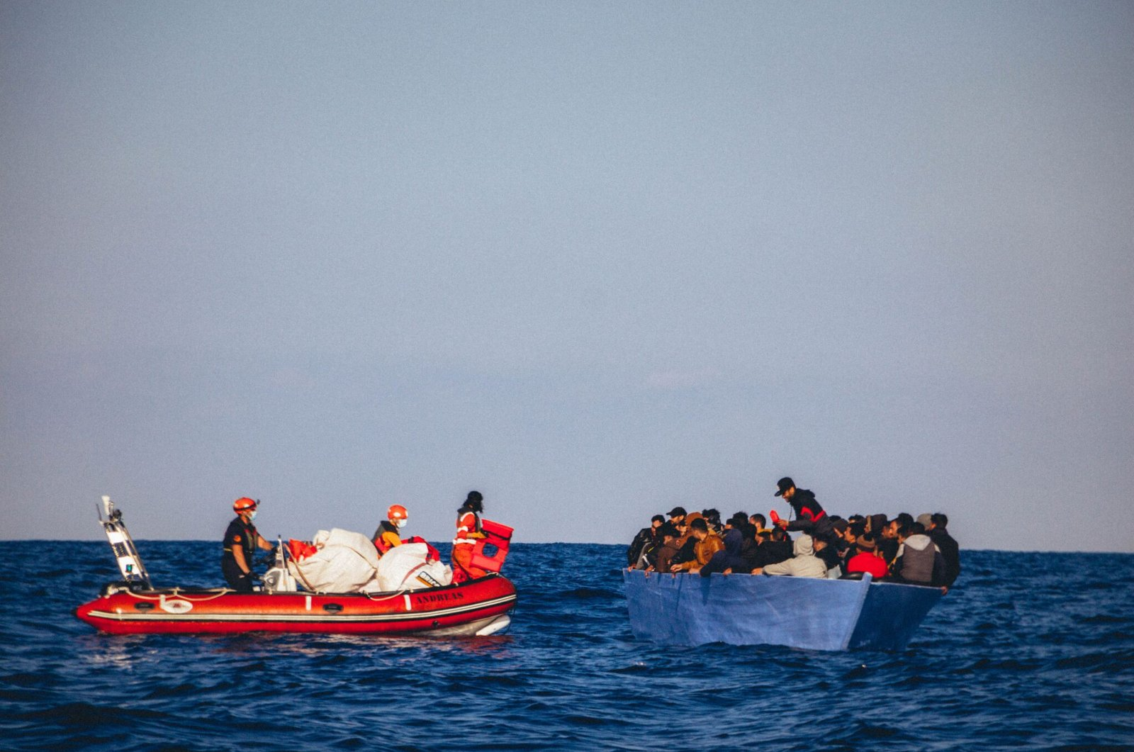 """A handout picture released by German migrant rescue NGO Sea-Eye and taken on April 6, 2020, shows members of the NGO on a rubber boat during an operation to rescue people from a small wooden boat in distress off the Libyan coast, before bringing them onboard their vessel """"Alan Kurdi"""". (AFP Photo)"""