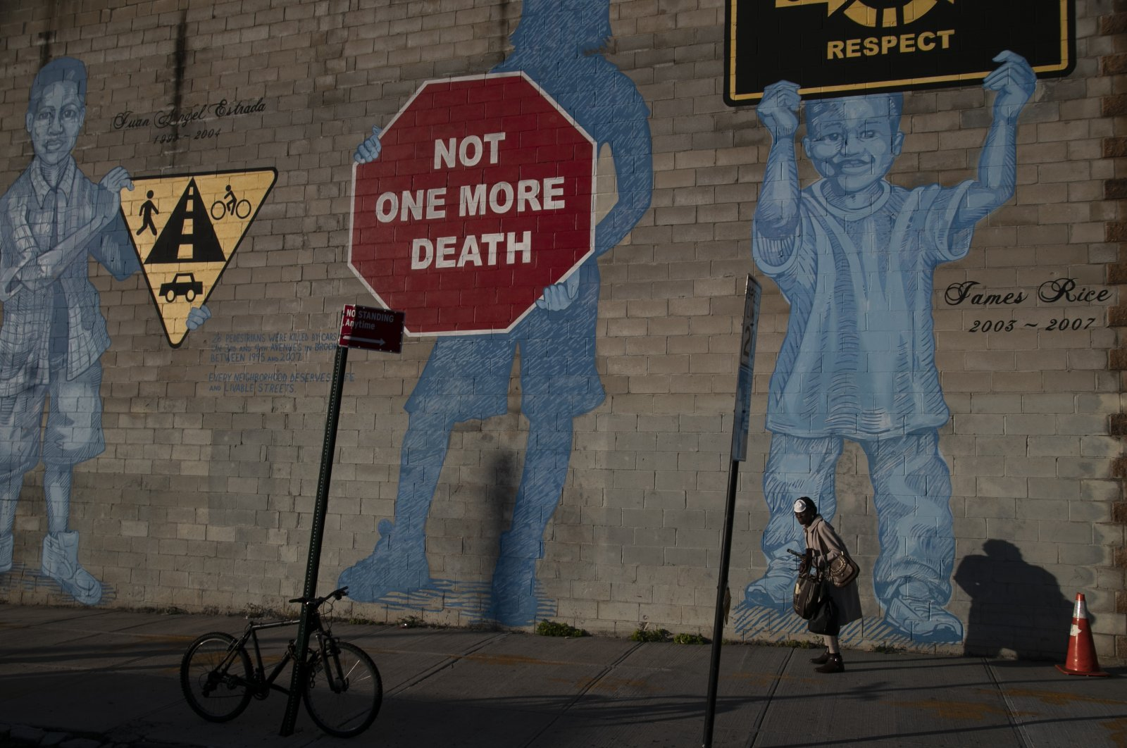 A woman with a face mask walks past a mural in the Brooklyn borough of New York City, March 27, 2020. (AP Photo)