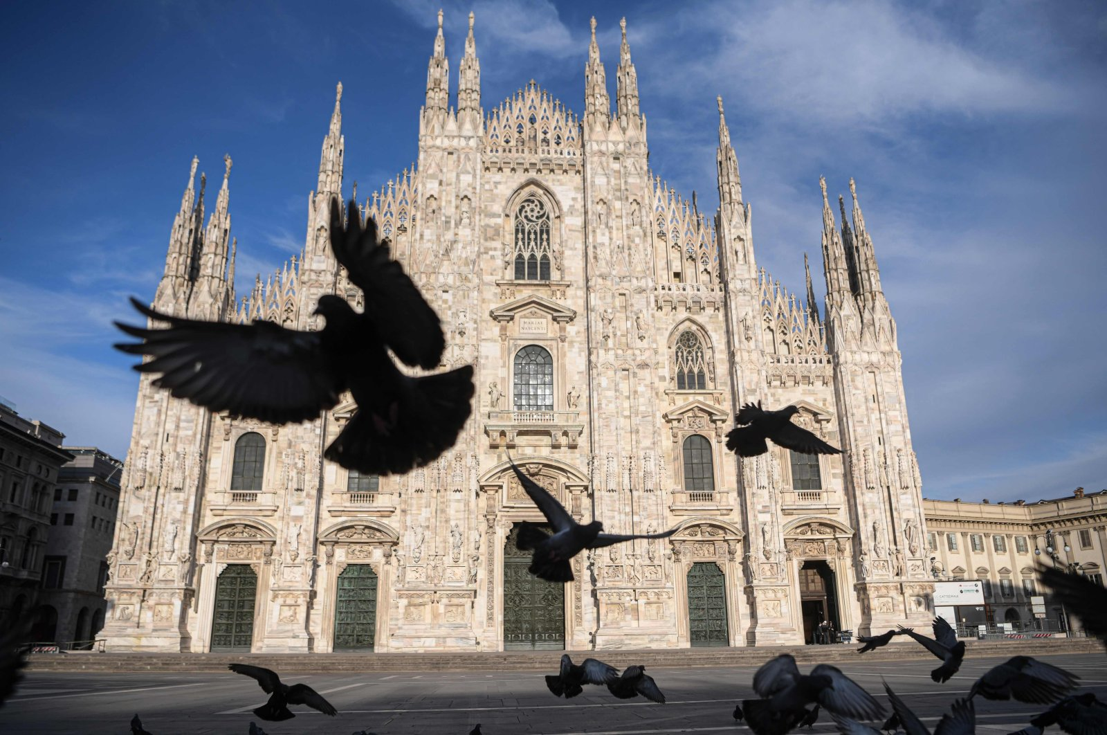 Pigeons fly over a deserted Piazza del Duomo during Italy's lockdown aimed at curbing the spread of the COVID-19 outbreak, in central Milan, Italy, April 12, 2020. (AFP Photo)