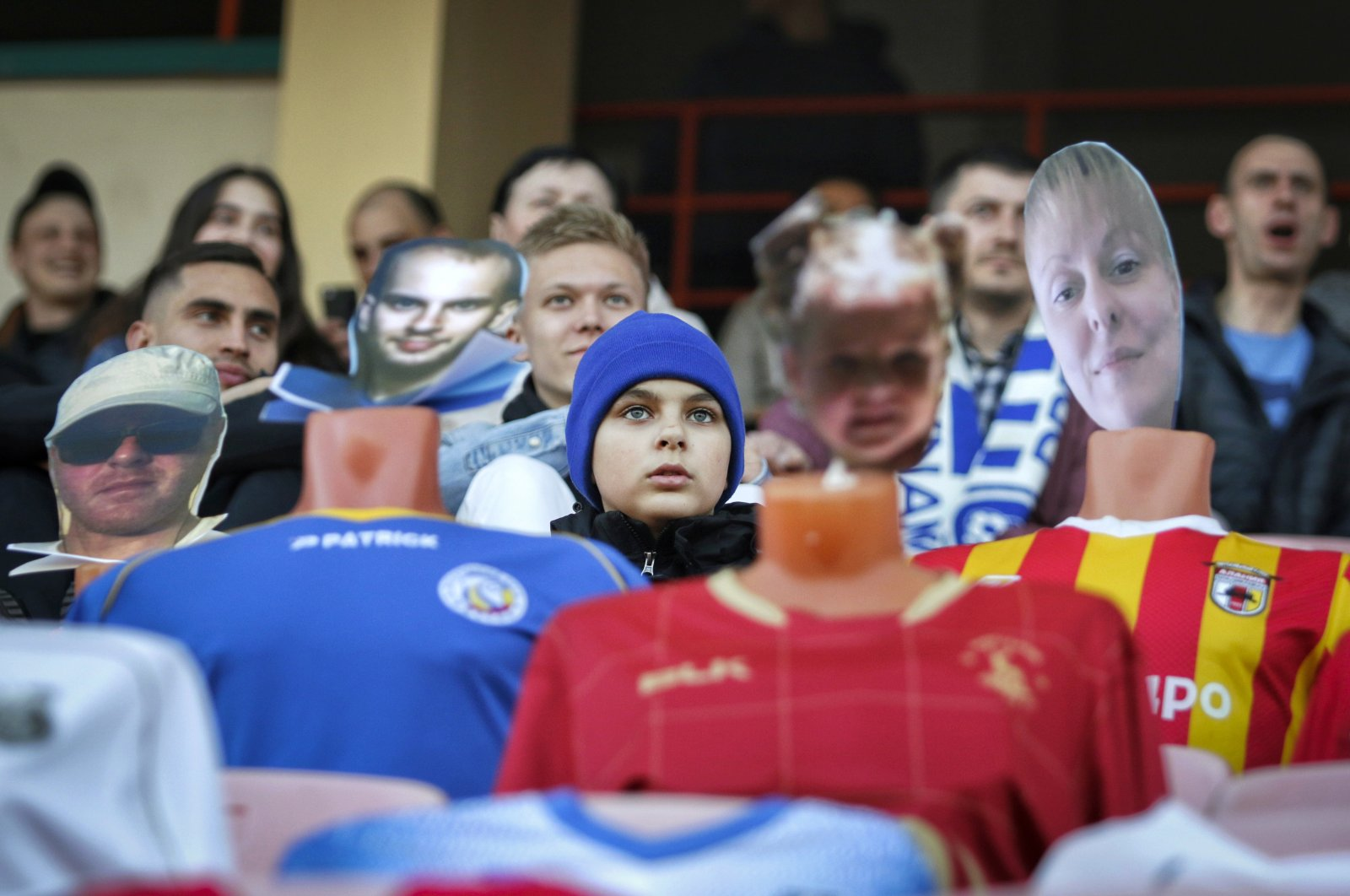 """Fans sit in the stands among mannequins in football uniforms with the faces of """"virtual fans"""" who bought tickets online during the match between FC Dynamo Brest and FC Shakhter Soligorsk in Brest, Belarus, April 8, 2020. (AP Photo)"""