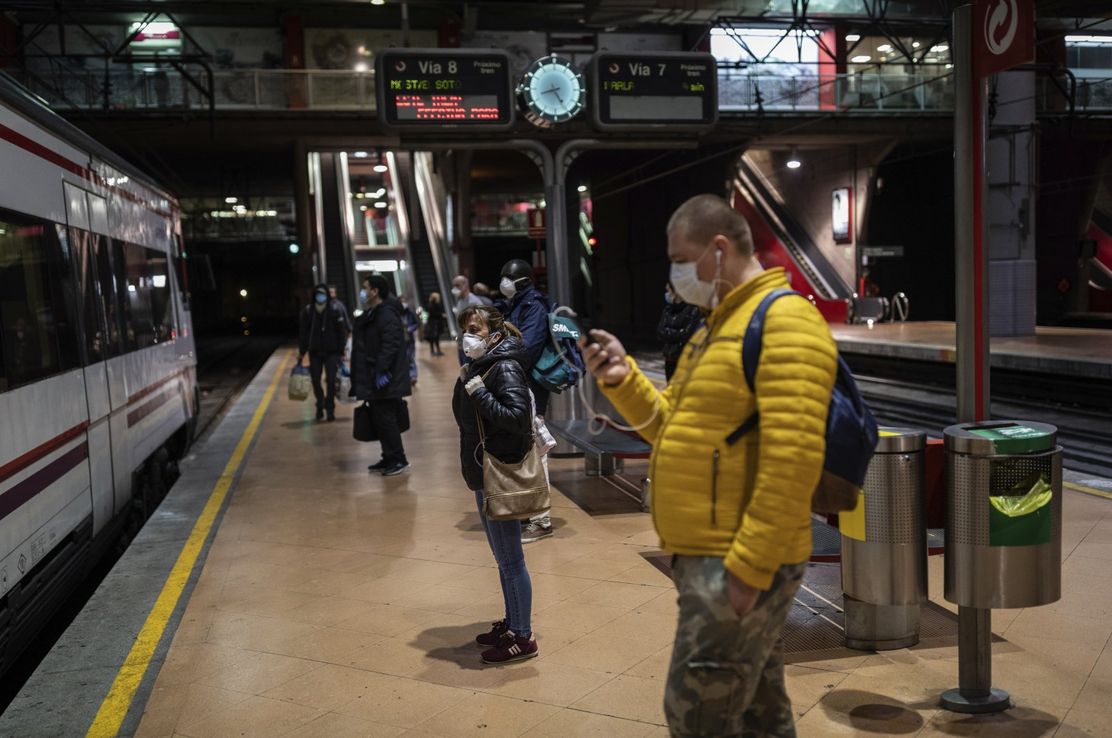 Commuters wear face masks to protect against the coronavirus while waiting on a platform at the Atocha train station, Madrid, April 13, 2020. (AP Photo)