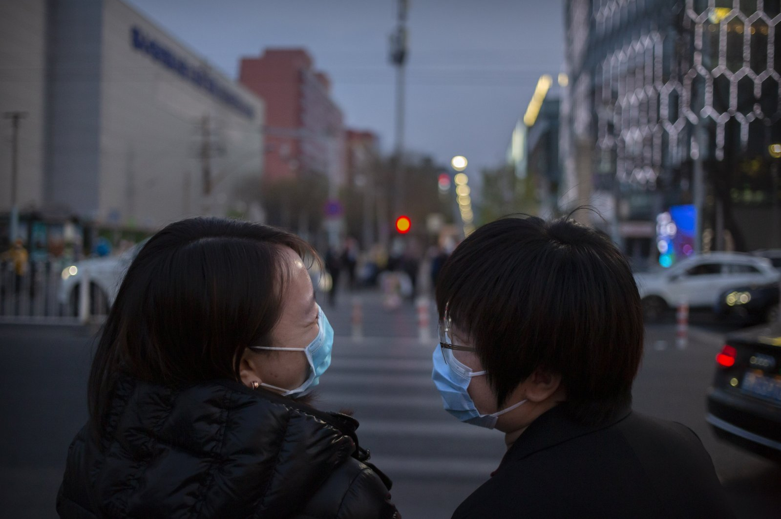 People wearing face masks to help curb the spread of the new coronavirus laugh as they cross an intersection in Beijing, Friday, April 10, 2020. (AP Photo)