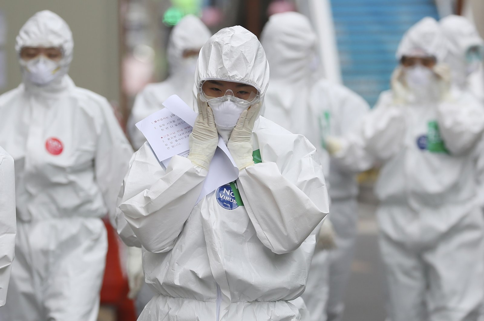 A medical staff member adjusts her face mask as she arrives for a duty shift at Dongsan Medical Center in Daegu, South Korea, Monday, April 13, 2020. (AP Photo)