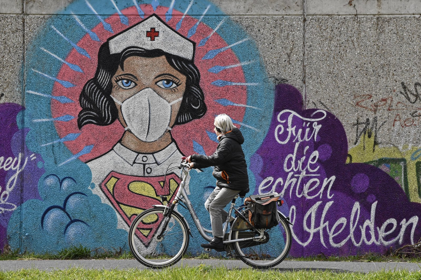 """A woman on a bicycle passes a coronavirus graffiti by street artist 'Uzey' showing a nurse as Superwoman, the lettering reads """"for the real heroes"""" on a wall in Hamm, Germany, on Easter Monday, April 13, 2020. (AP Photo)"""