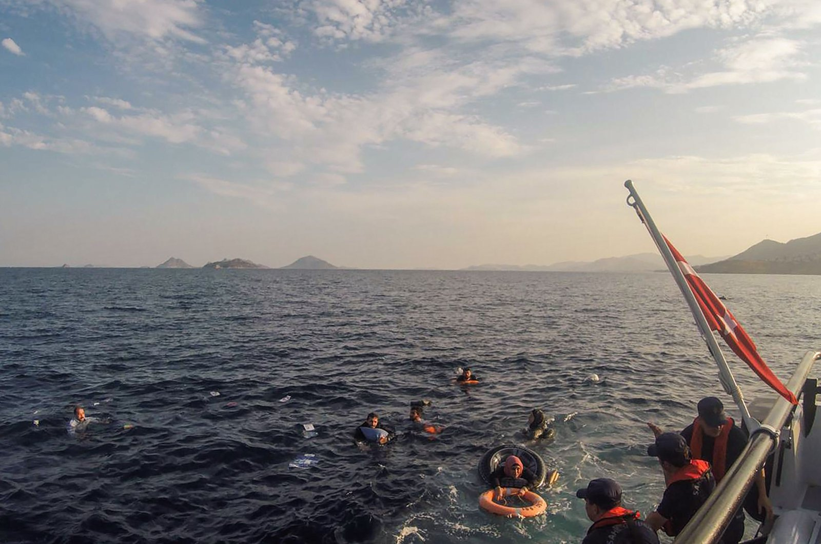 This handout picture released and taken on June 17, 2019 by the Turkish coastguard shows illegal migrants being rescued after their boat sank in the Aegean sea, off the coast of southwestern Turkey. (AFP Photo)