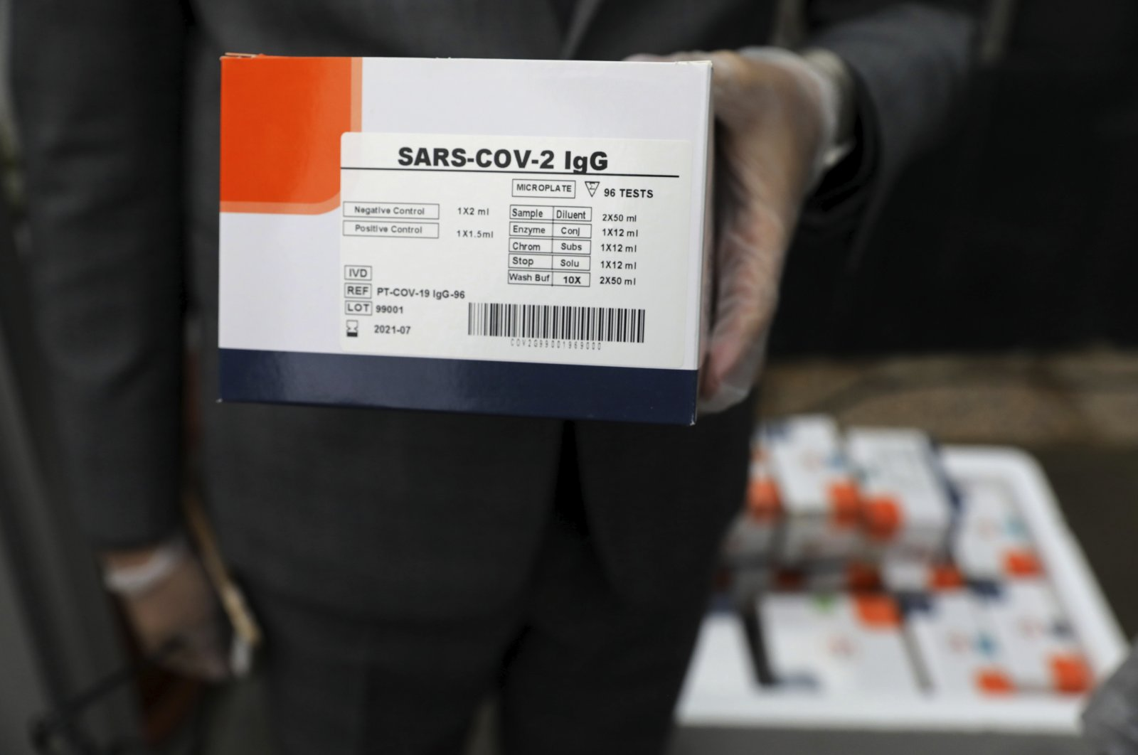 A medical firm staff member holds a coronavirus testing kit at a medical firm just outside Tehran, Iran, April 11, 2020. (AP Photo)