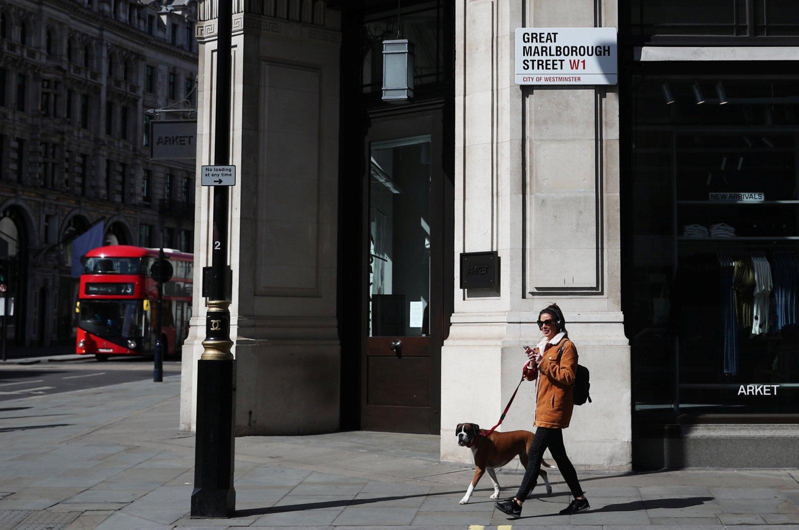 A woman walks her dog along Great Marlborough Street, London, April 13, 2020. (Reuters Photo)