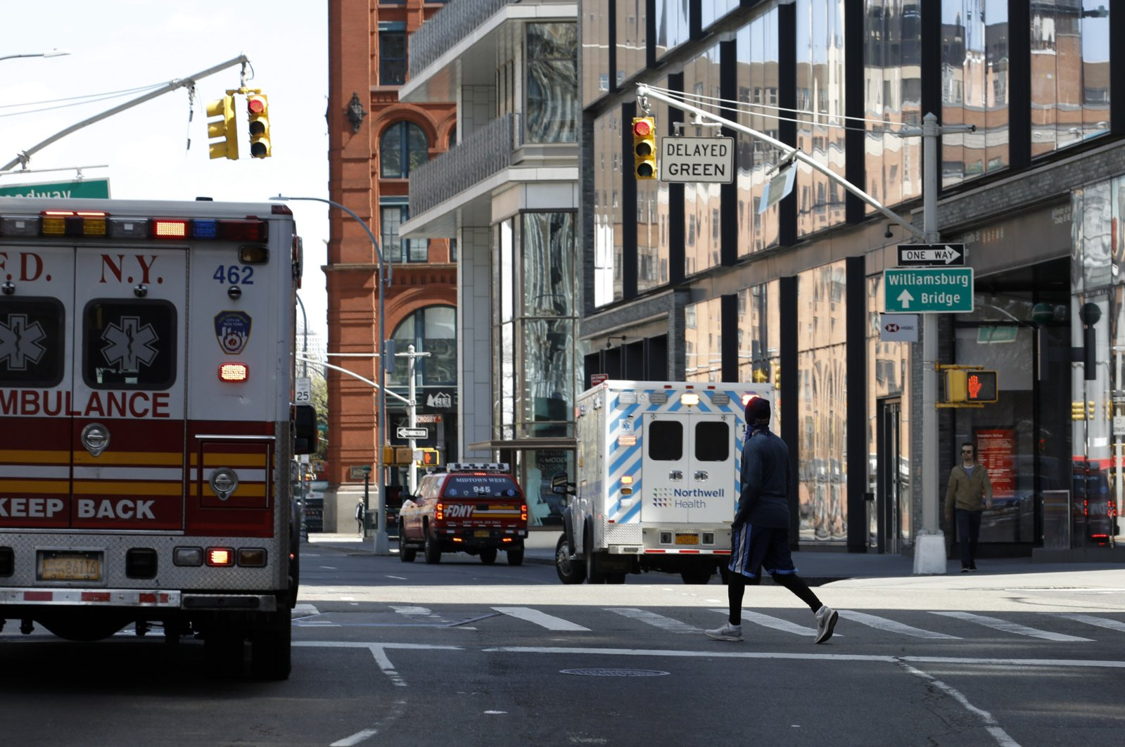 A man crosses the street past New York City Fire Department emergency service trucks and ambulances along West Broadway, New York, April 11, 2020. (EPA Photo)