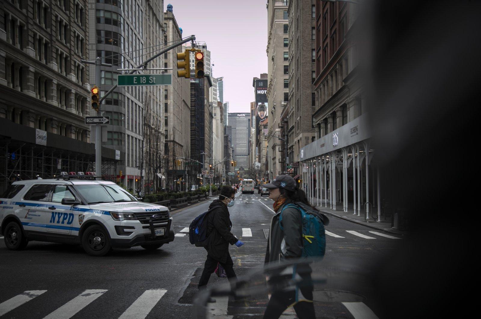 Pedestrians, one wearing a face mask, cross Park Avenue, New York City, New York, U.S., March 25, 2020. (AP Photo)