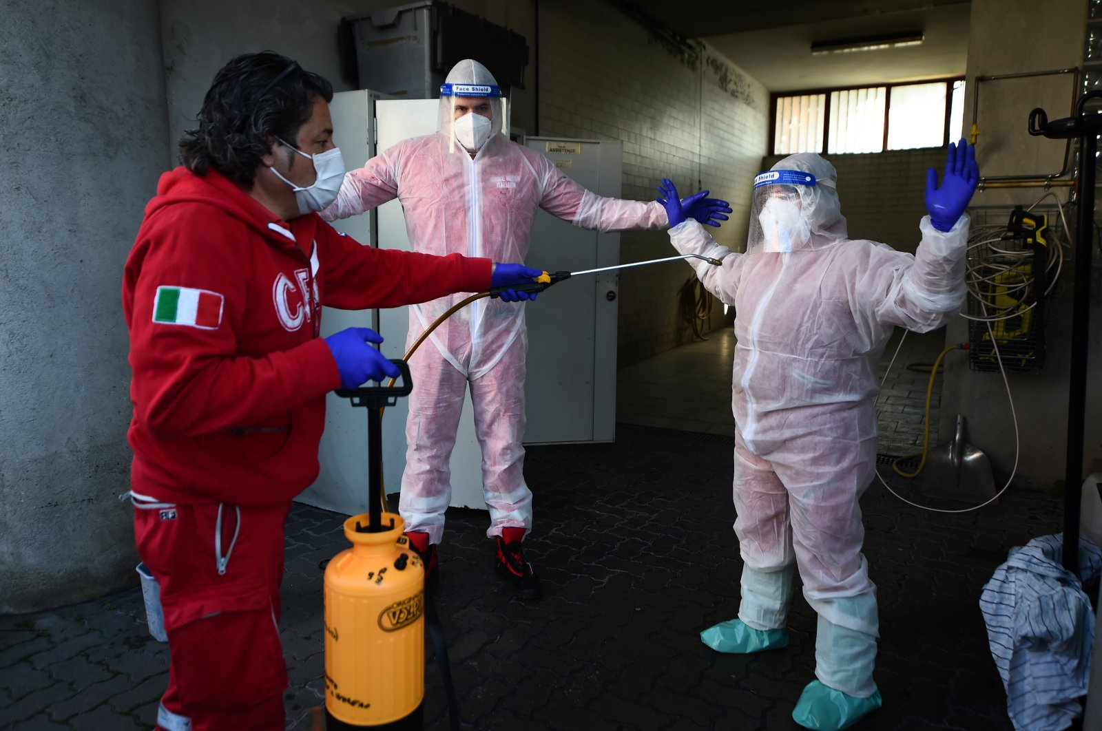 Red Cross volunteer sprays disinfectant on colleagues returning from an intervention on a patient suffering from the coronavirus on Easter Sunday as Italy remains on lockdown, in Turin, Italy, April 12, 2020. (Reuters Photo)