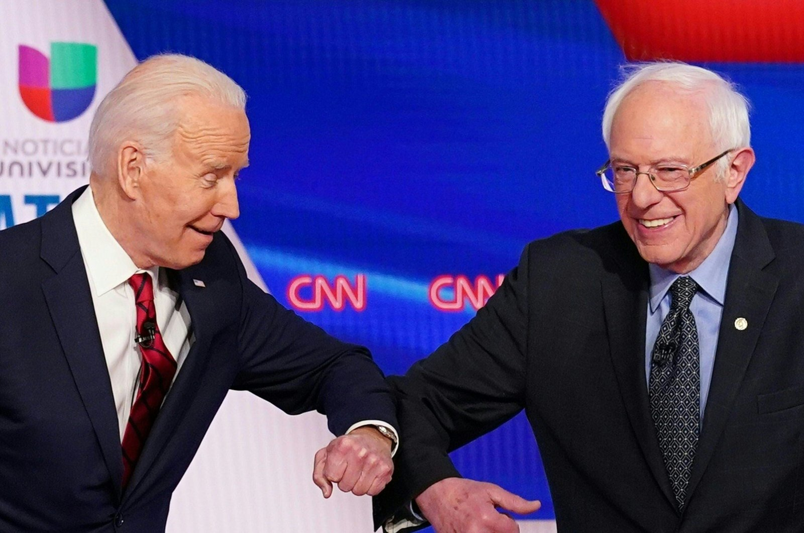 Joe Biden (L) and Senator Bernie Sanders greet each other with a safe elbow bump before the start of the 11th Democratic Party 2020 presidential debate in a CNN Washington Bureau studio in Washington, March 15, 2020. (AFP Photo)