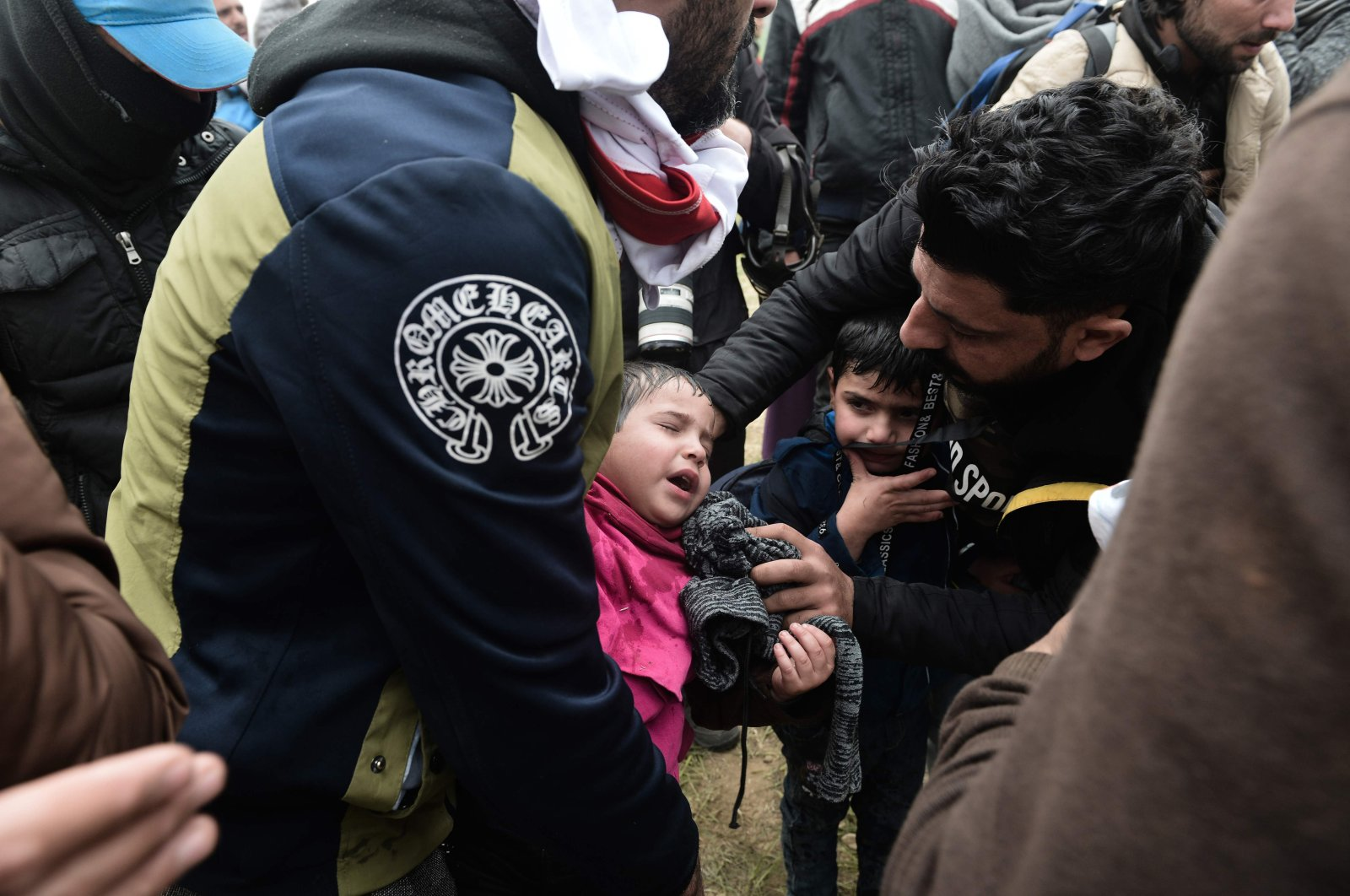 A child suffers from tear gas used by Greek riot police outside of a refugee camp in Diavata, a west suburb of Thessaloniki, where migrants gather on April 6, 2019. (AFP Photo)