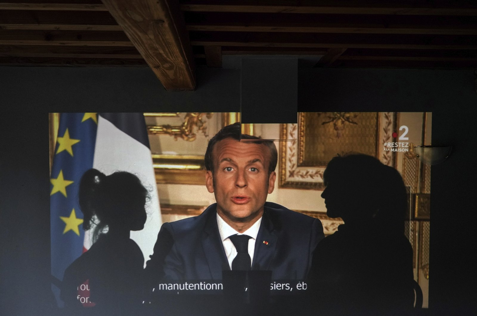 A family watches French President Emmanuel Macron's televised speech, on April 13, 2020, in Lyon, central France. (AP Photo)