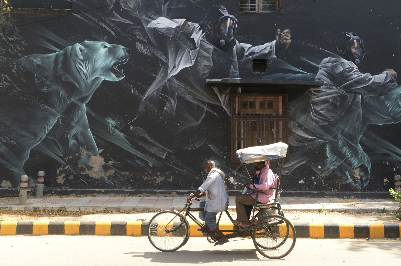 A rickshaw driver carries passengers wearing facemasks past a mural at Lodhi Art District during a government-imposed nationwide lockdown as a preventive measure against the COVID-19 coronavirus, in New Delhi on April 13, 2020. (Photo by SAJJAD HUSSAIN / AFP)
