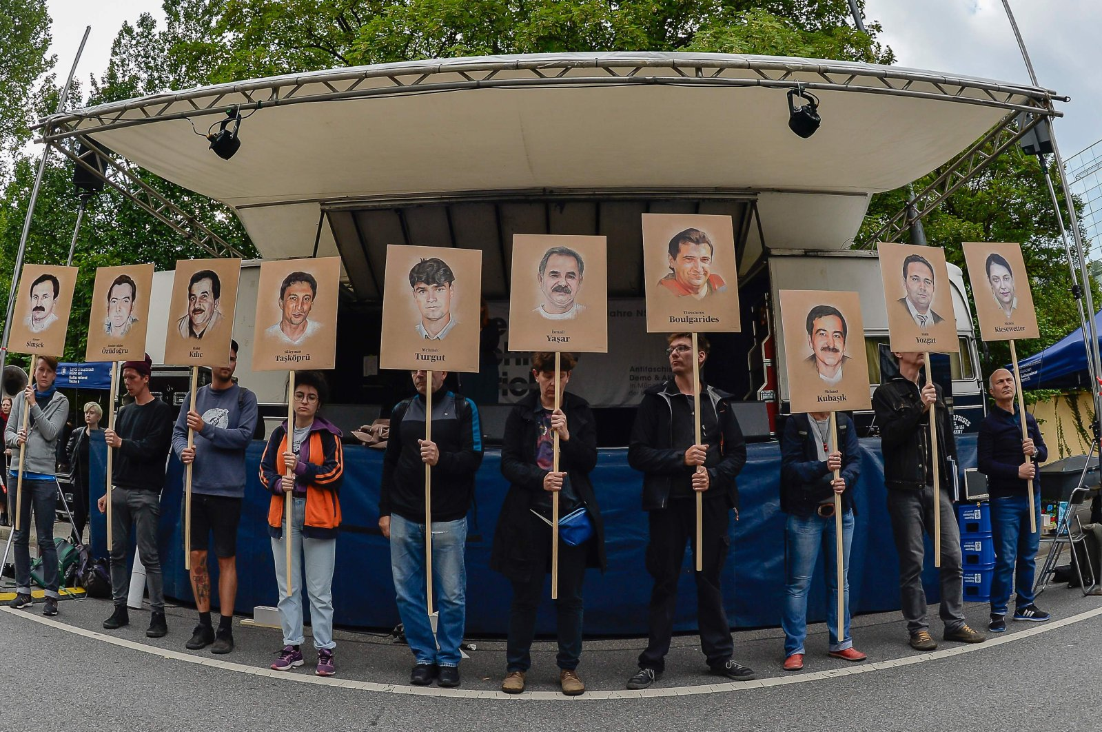 Protesters hold up signs with pictures of the victims of the neo-Nazi cell National Socialist Underground (NSU) before the proclamation of the sentence in the trial against Beate Zschaepe, the only surviving member of the NSU behind a string of racist murders, in Munich, Germany, July 11, 2018. (AFP Photo)