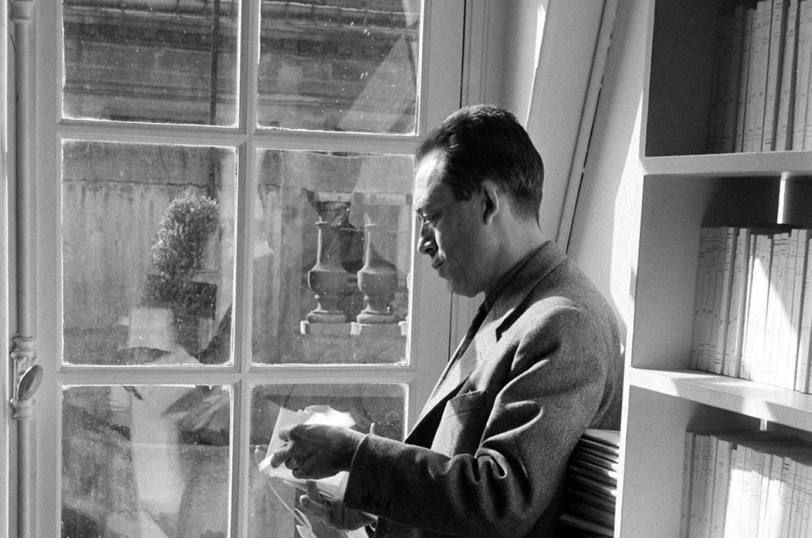 French writer Albert Camus reads outside his publishing firm's office, Paris, 1957.