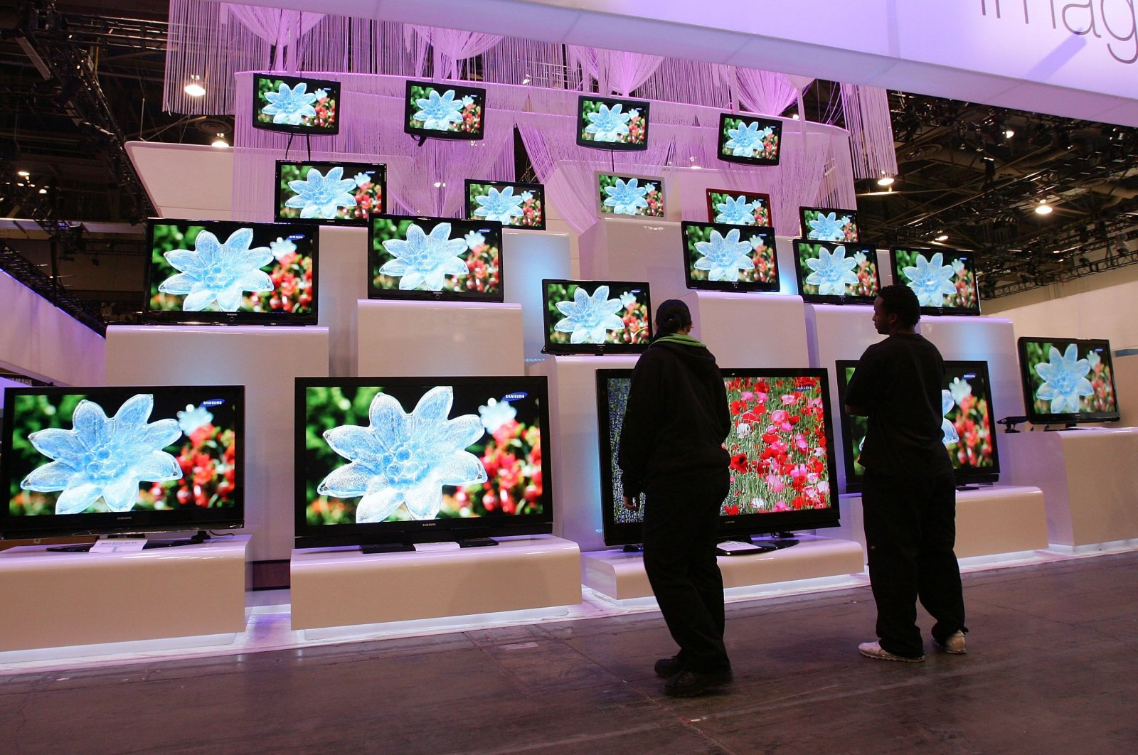 Workers look at a display of televisions by Samsung at the Las Vegas Convention Center in Las Vegas, Nevada, Jan. 5, 2007. (AFP Photo)