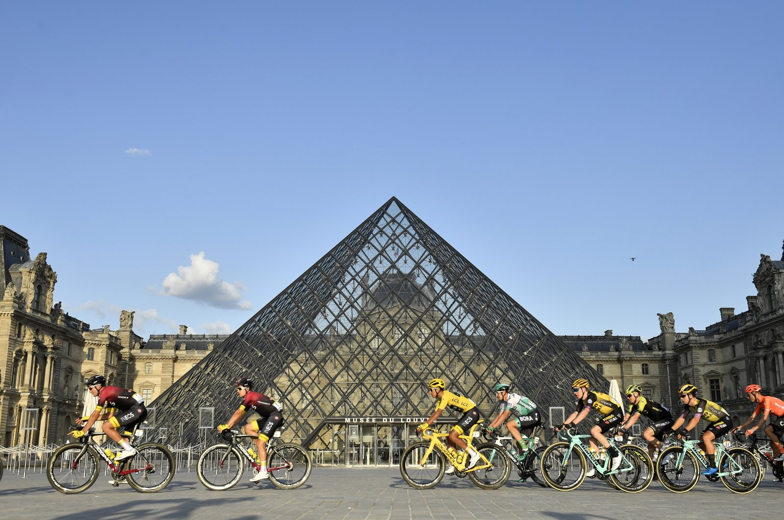 Colombia's Egan Bernal (C) wearing the overall leader's yellow jersey passes by the pyramid of the Louvre museum with the pack during the final stage of the Tour de France cycling race, Paris, France, July 28, 2019. (AP Photo)