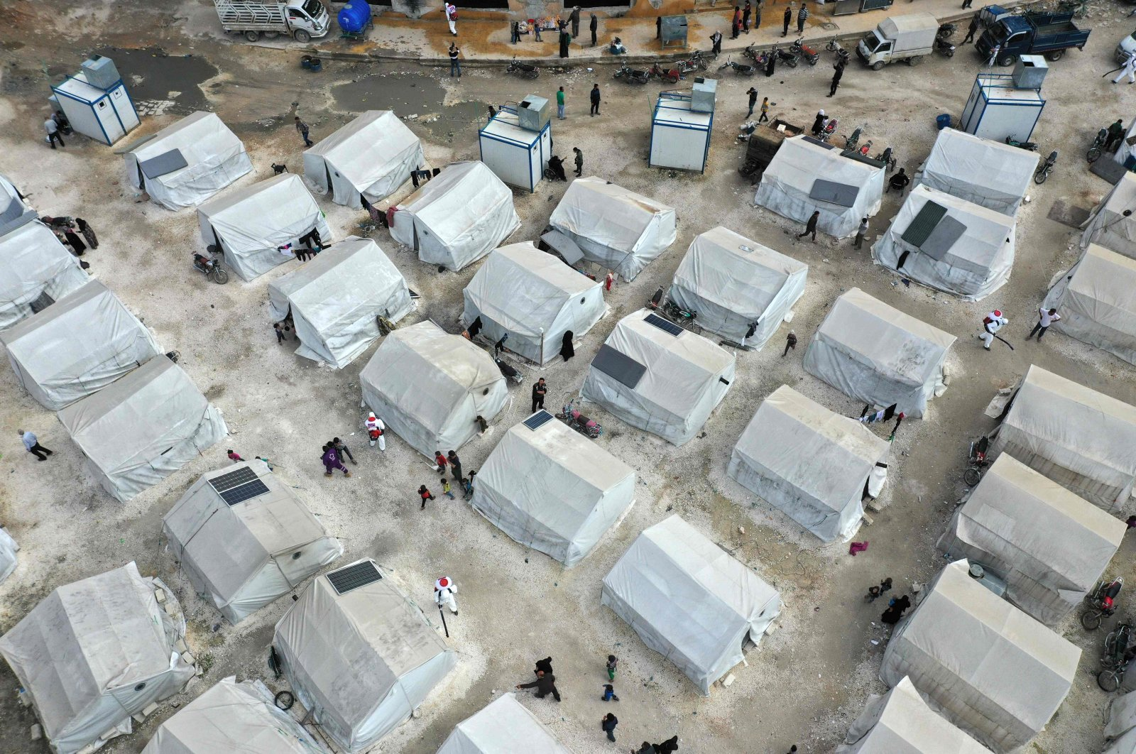 A drone image taken on April 9, 2020, shows sanitation workers disinfecting a camp for displaced Syrians next to the Idlib municipal stadium in the northwestern Syrian city, during a campaign to limit the spread of the coronavirus pandemic. (AFP Photo)