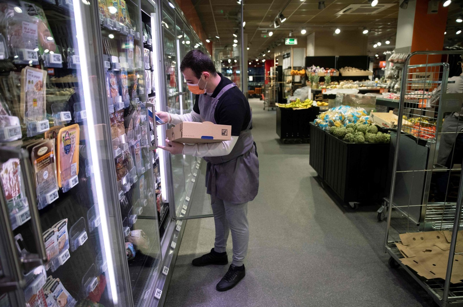 An employee wearing a protective mask stocks the cold shelves, before the opening of a Franprix supermarket, Paris, April 8, 2020. (AFP Photo)