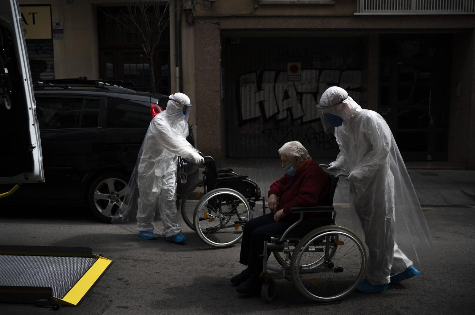 A volunteer of the Spanish NGO Open Arms pushes an elderly resident of a nursing home with coronavirus symptoms in a wheelchair to a hospital, Barcelona, Spain, April 11, 2020. (AP Photo)