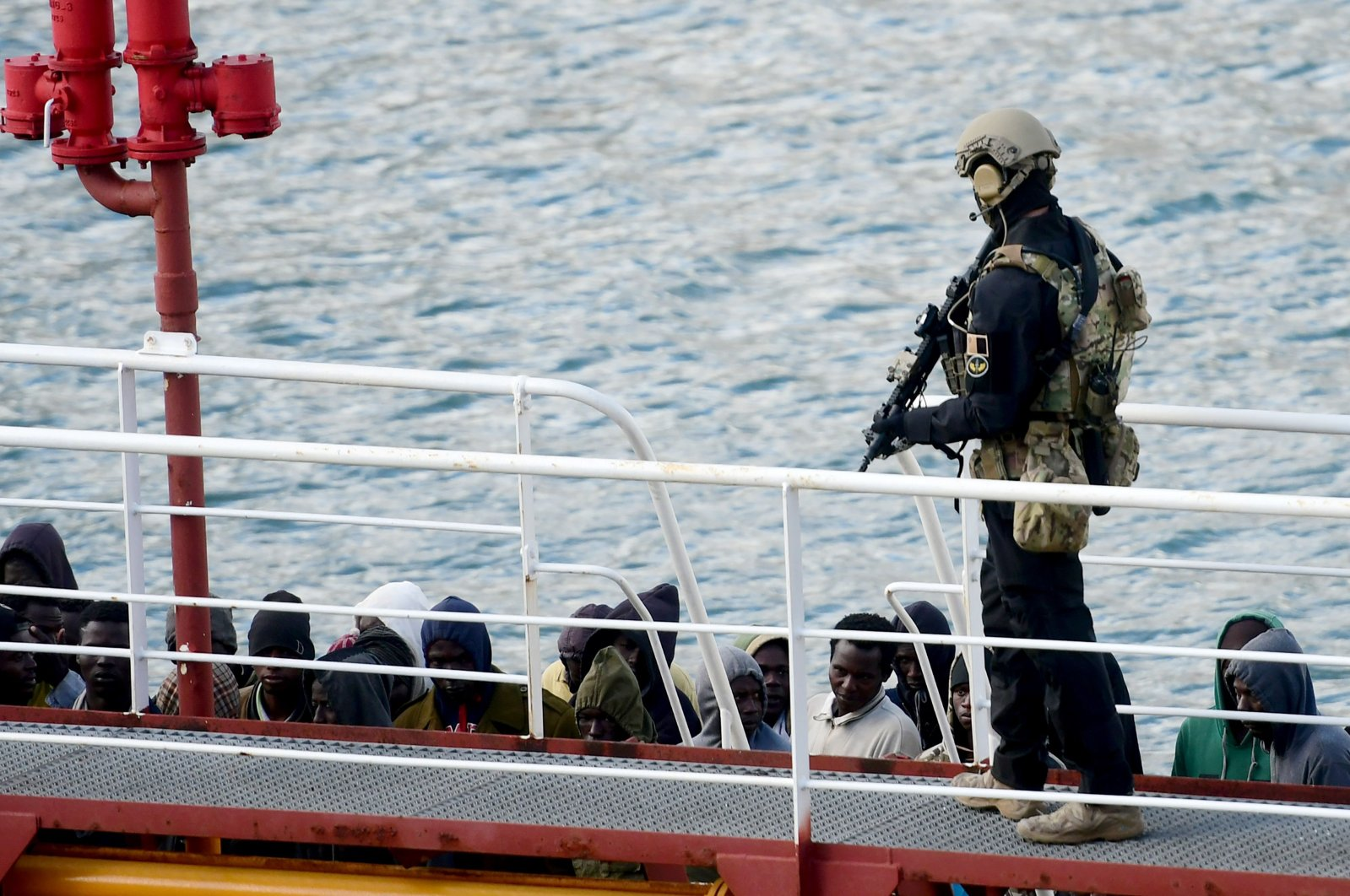 An armed policeman stands guard after migrants disembarked from the Motor Tanker El Hiblu 1 that was hijacked by migrants in Valletta's Grand Harbour on March 28, 2019, after Maltese armed forces took control of the vessel. (AFP Photo)